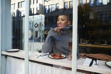 Young woman sitting in cafe with food, seen through window