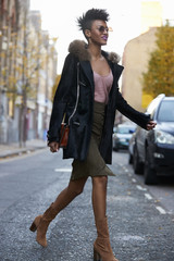 Fashionable woman in coat and skirt crossing street, close up