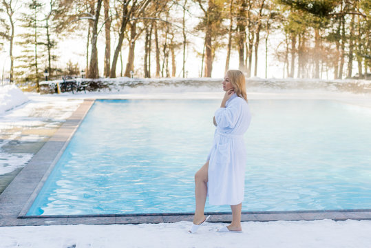 Young blonde woman in bathrobe near outdoor swimming pool at winter day