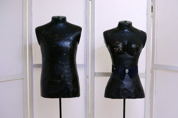 Male and female mannequins stand on a light background. Dark-colored mannequins
