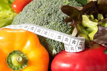 Ein Messband und verschiedene Gemüse für eine Diät