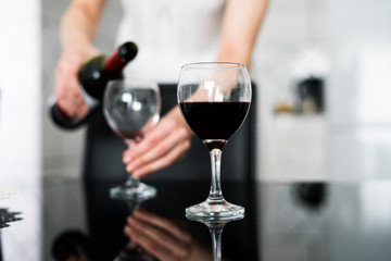 Woman pouring red wine in a wine glass