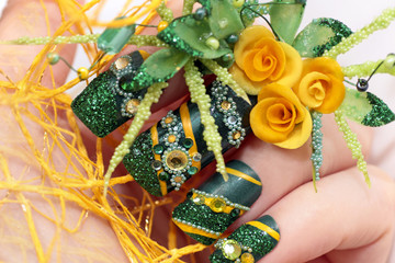 Nail design with acrylic yellow roses and leaves hand-female hand with sequins,rhinestones,beads on a white background closeup.