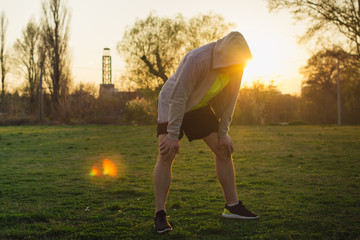 Young man taking breath after jogging