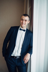 Smiling groom with short hair leans on the windowsill while he poses in the room