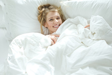 Woman in the morning smiling in bed