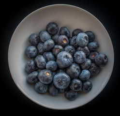 Natural looking blueberries in white cup. Selective focus.