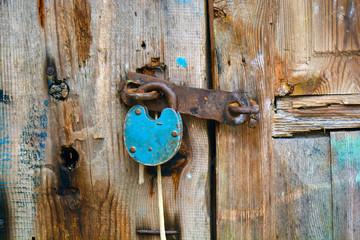 Old rusty padlock hanging on an old wooden door