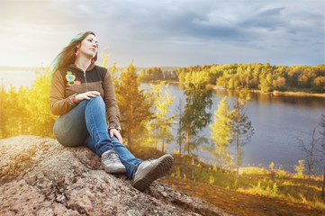 Woman traveler sitting on the cliff. Travel and freedom concept