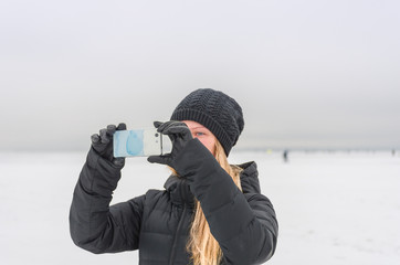 Woman taking pictures on the phone winter landscape