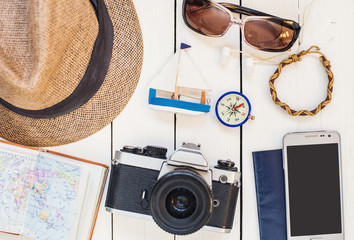 Accessories for travel. Different objects on wooden background. Passport, photo camera, smart phone, sunglasses and travel map. Top view. Tourism, holidays and tourism concept