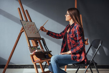Pretty Pretty Girl artist paints on canvas painting on the easel. Studio black background. Long hair, brunette.