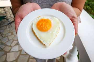 woman hand holding fried eggs in ideal heart on the white plate