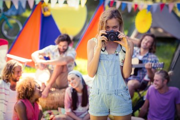 Portrait of woman taking a picture of friends at campsite