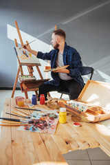 Designed by artist man finishing his masterpiece holds a brush in hand.