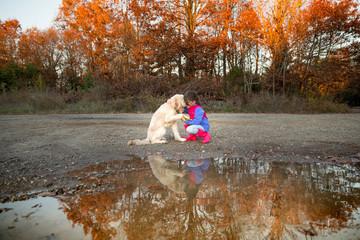 Girl crouching, holding dog's paw
