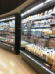 Selection of yogurts, soy milk and milk on the shelves in a supermarket