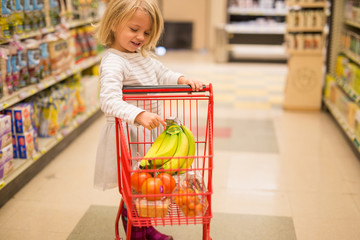 Girl filling shopping trolley in supermarket
