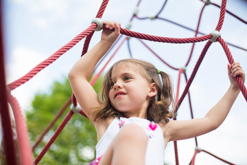 Girl holding ropes in playground