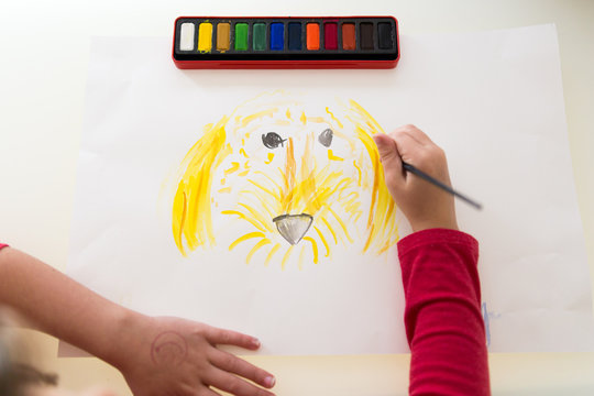 Child painting a picture of a dog
