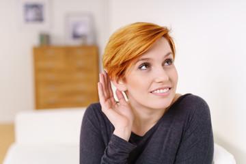 frau hält eine hand an ihr ohr um besser zu hören