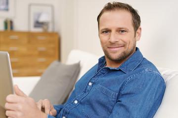 lächelnder mann sitzt auf dem sofa und arbeitet am laptop