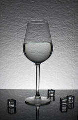 Glass of ice water on gray background