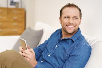 lächelnder mann tippt eine nachricht auf seinem mobiltelefon