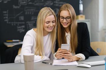 zwei kolleginnen schauen gemeinsam auf ein mobiltelefon
