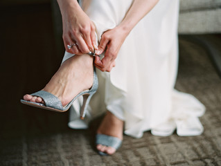 Bride tying silver colour sandals