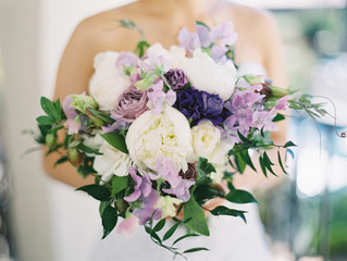 Bride holding white and purple rose bouquet