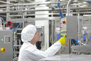 technician at control panel in factory - pressing buttons