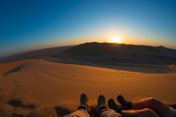 Colorful sunset over the Namib desert, Namibia, Africa. Scenic sand dunes in backlight in the Namib Naukluft National Park. Hiking boots in the foreground. Fish eye view.