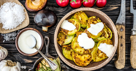 fried zucchini with sour cream and spices on wooden table, top view