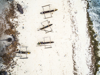 many wooden fishing boats on african seashore on Zanzibar, top view, aerial photo
