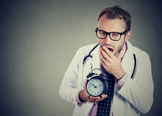 Sleepy, exhausted doctor holding alarm clock, yawning, tired after busy day