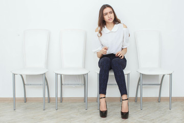 A beautiful girl is sitting on chair and angry