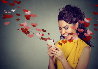 Happy woman sending love text message on mobile phone