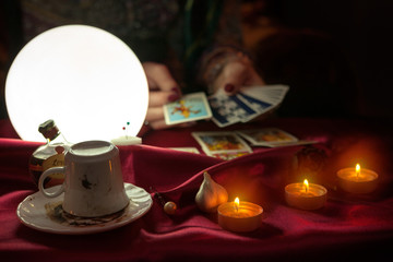 Cofee cup, candles and shiny crystal ball with tarot card in hand of fortune teller woman