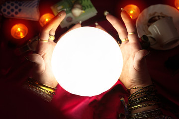 Gypsy woman fortune teller put her hands around crystal ball