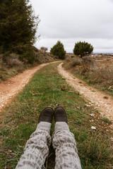 Vista en primera persona de una mujer sentada en el inicio de un camino