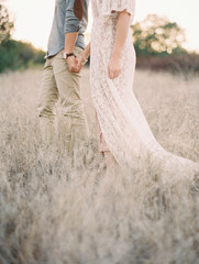 Couple holding hands in meadow, close up