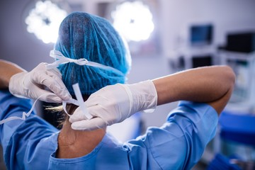 Female nurse tying surgical mask in operation theater