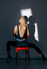 woman sit on a red chair; blue background
