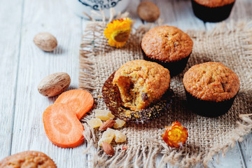 hearty and healthy breakfast, lunch, pastries, carrot cupcakes with raisins, candied fruits, nuts and green tea on a wooden background