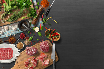 Overhead view of colorful roast vegetables, savory sauces and salt served with grilled t-bone steak on a rustic wooden counter in a country steakhouse