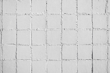 Texture and old square tiles of beige white color tile wall