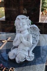 betende engelsfigur kniet an einem grabstein