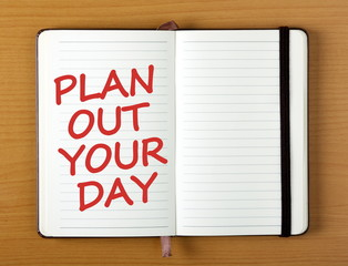 The words Plan Out Your Day in red text on the open page of  notebook as a reminder to organize your schedule for greater productivity