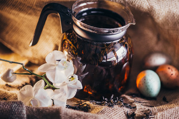 black tea and easter eggs on the sackcloth background